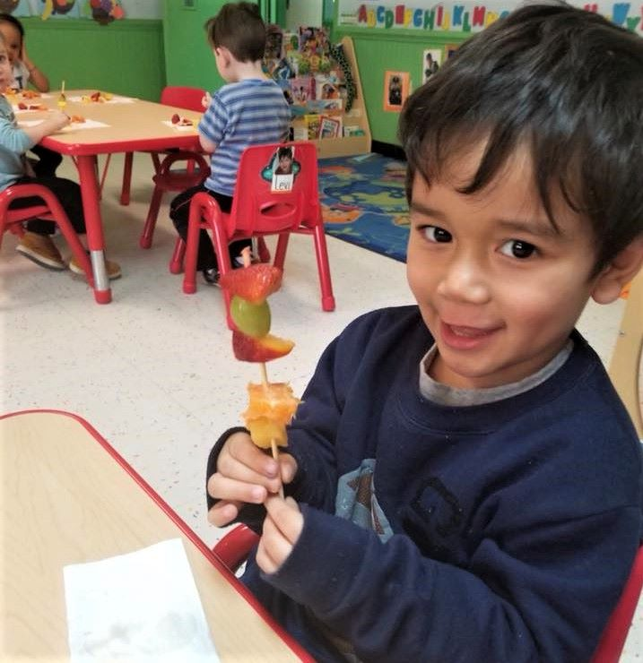 A preschool boy putting some chunks of different fruits for their school activity at a Preschool & Daycare Serving Hampton Roads, VA