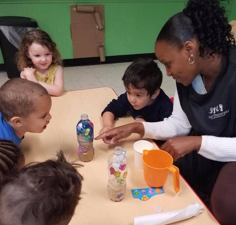 Preschoolers getting amazed with their teacher on a sand in a bottle activity at a Preschool & Daycare Serving Hampton Roads, VA