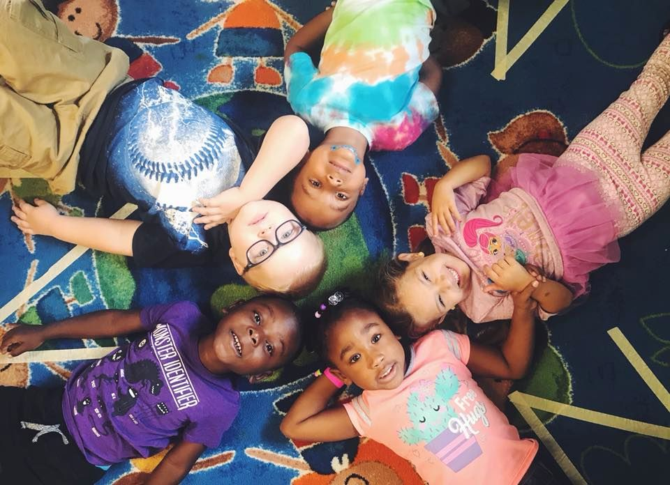 Group of preschool kids very happy and lying around at a Preschool & Daycare Serving Hampton Roads, VA