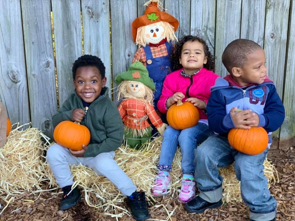 Happy little young preschool kids holding a pumpkin while sitting on wood chips on a scarecrow background at a Preschool & Daycare Serving Hampton Roads, VA