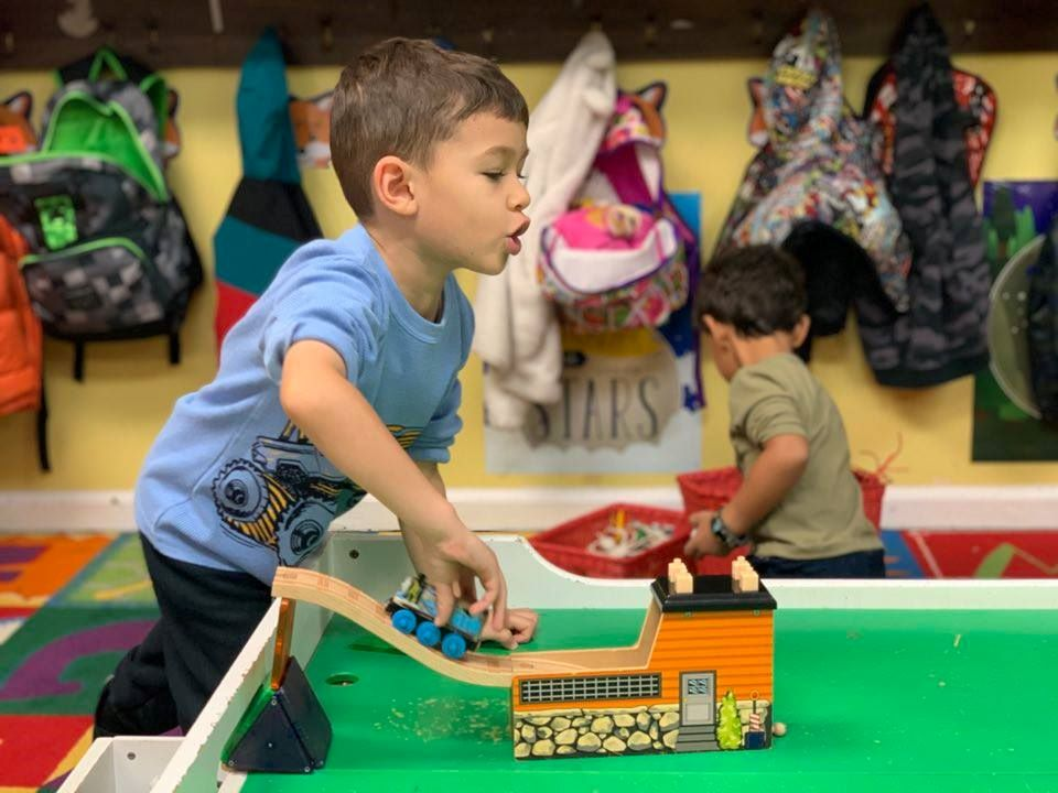 A young boy having fun playing a train toy at a Preschool & Daycare Serving Hampton Roads, VA