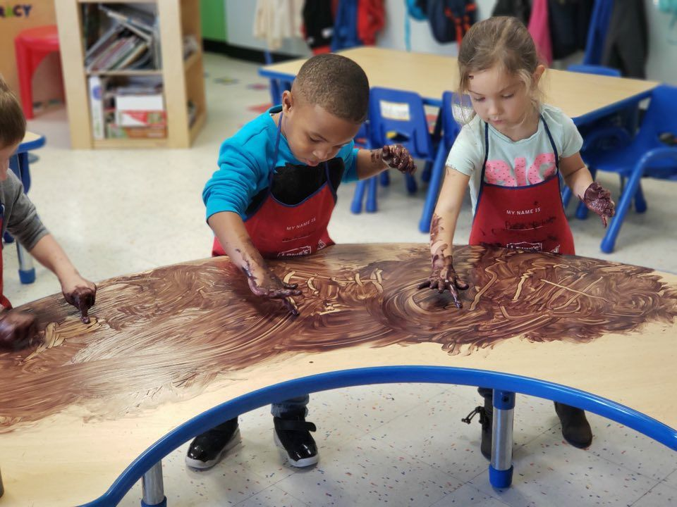 Group of preschoolers doing a finger painting on their classroom table at a Preschool & Daycare Serving Hampton Roads, VA