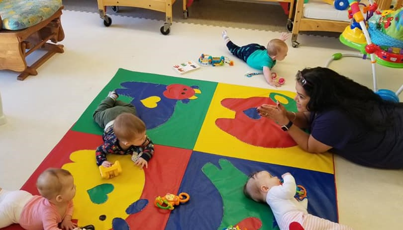 Cute babies playing around with their toys being watched by a teacher while singing to them a nursery rhyme at a Preschool & Daycare Serving Hampton Roads, VA