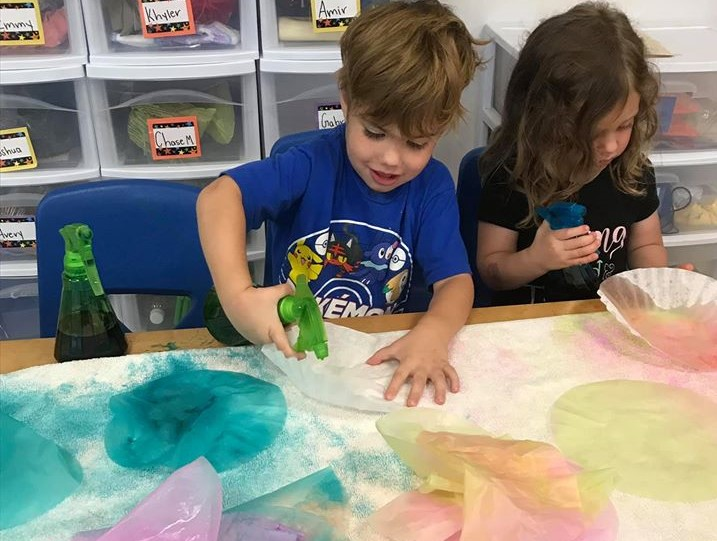 Preschoolers spraying some colored water in a spray bottle having fun on their water coloring art activity at a Preschool & Daycare Serving Hampton Roads, VA