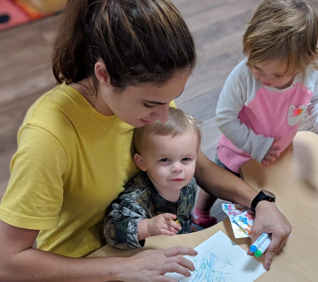 Pretty nursery teacher with cute little toddlers doing a crayon activity at a Preschool & Daycare Serving Hampton Roads, VA