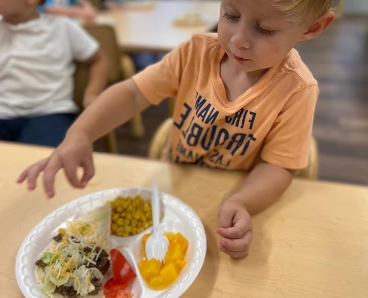 nursery boy eating corn, chunks of mango and strawberry and salad, a healthy food at a Preschool & Daycare Serving Hampton Roads, VA