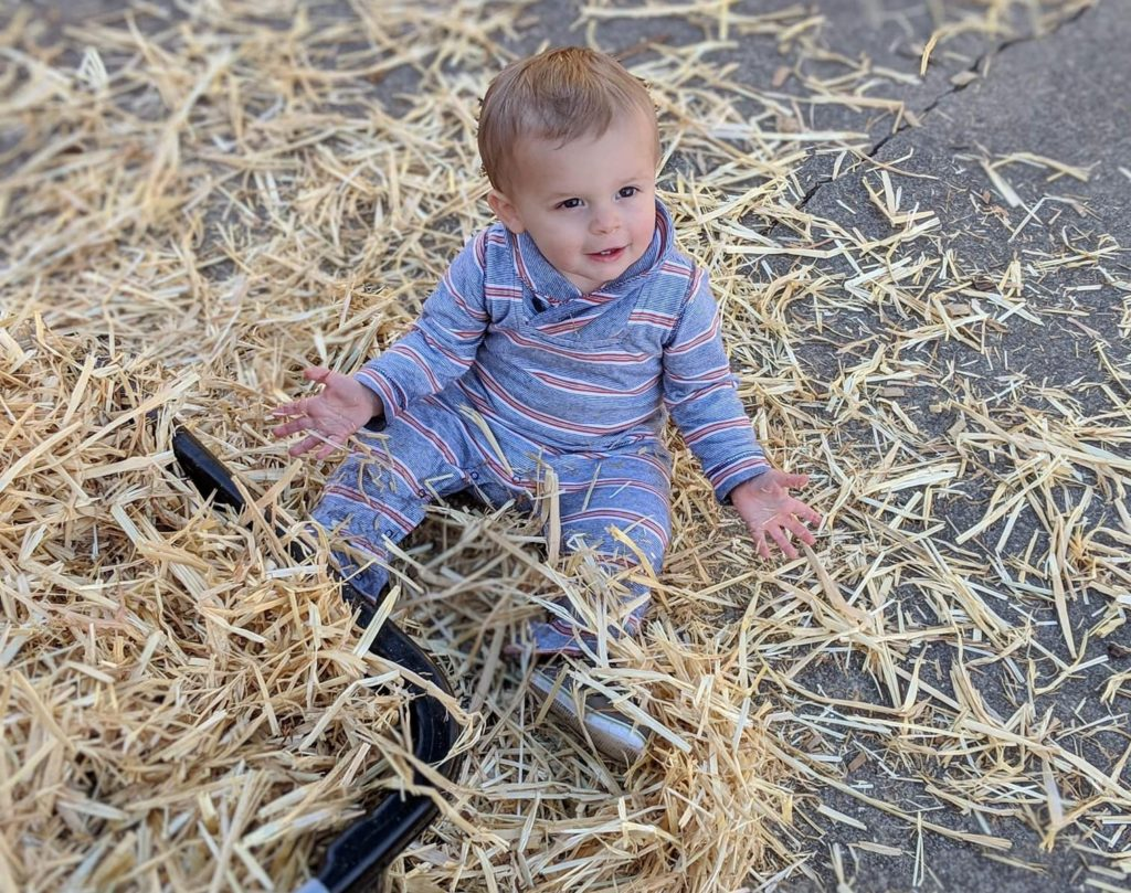 Cute little baby boy enjoying and playing with wood chips at a Preschool & Daycare Serving Hampton Roads, VA