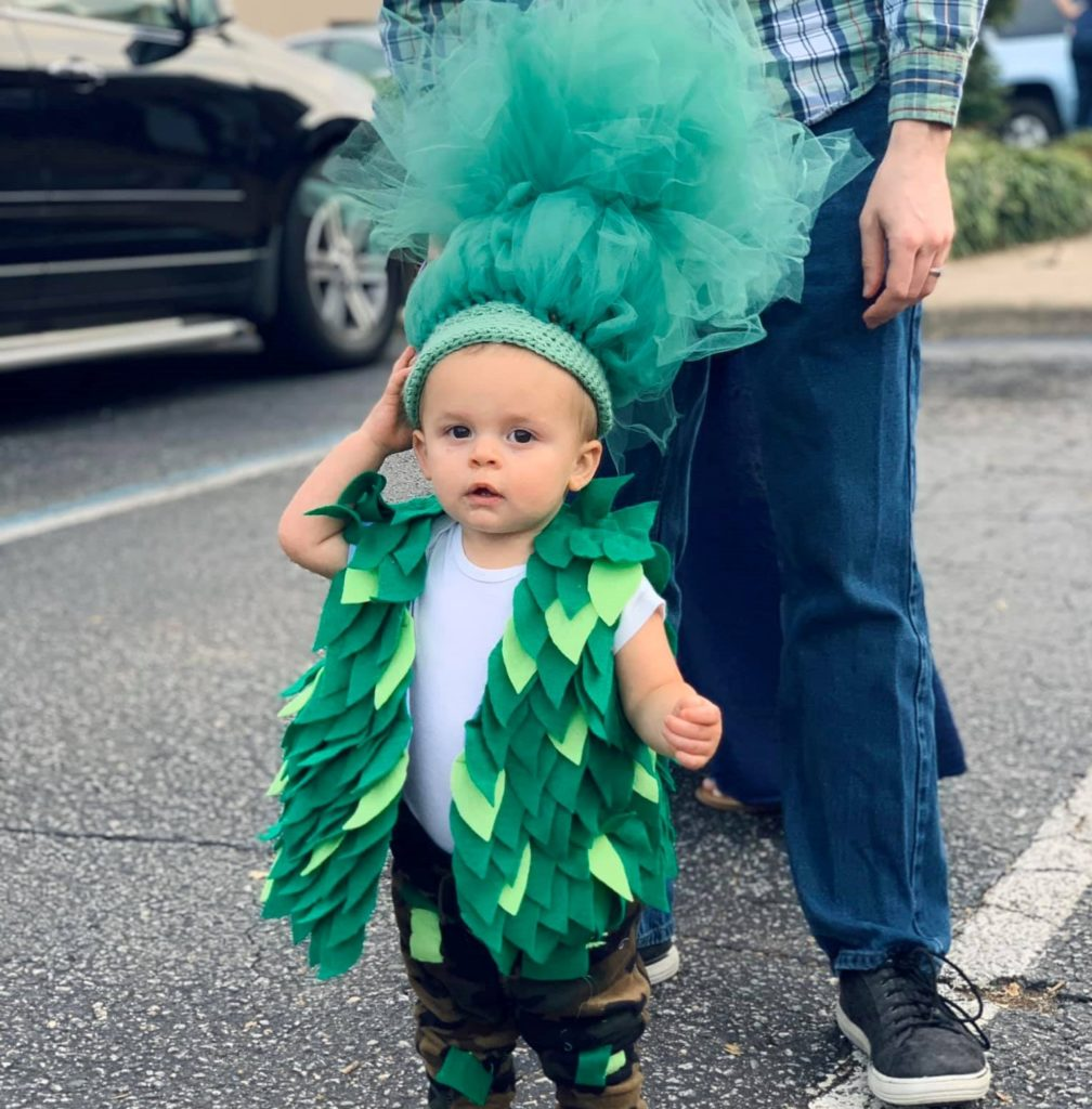 A young little boy wearing a green tree-like leafy costume on a parade at a Preschool & Daycare Serving Hampton Roads, VA