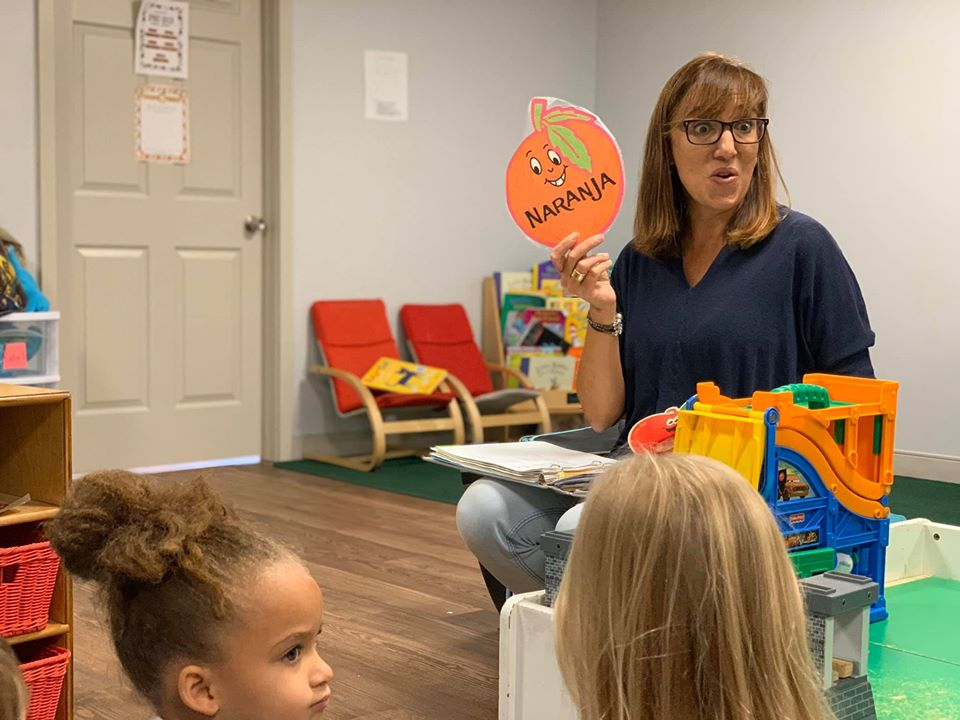 Teacher showing the preschool kids a Naranja (Spanish) picture on her hands which means Orange fruit in English at a Preschool & Daycare Serving Hampton Roads, VA