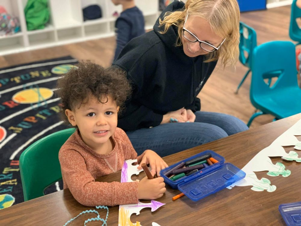 A preschool boy being watched by his teacher cutting and coloring a paper on their art activity at a Preschool & Daycare Serving Hampton Roads, VA