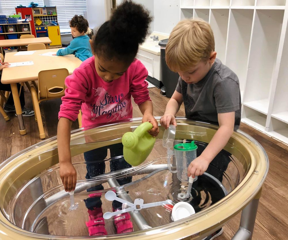 A little preschool girl and a boy enjoying their water activity on a clear water table with accessories at a Preschool & Daycare Serving Hampton Roads, VA