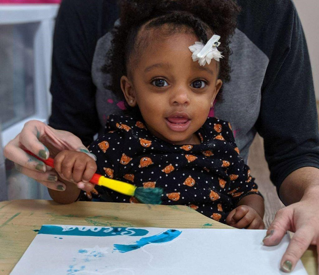 Cute little African American baby girl with her teacher enjoying a coloring a fish on a paper activity at a Preschool & Daycare Serving Hampton Roads, VA