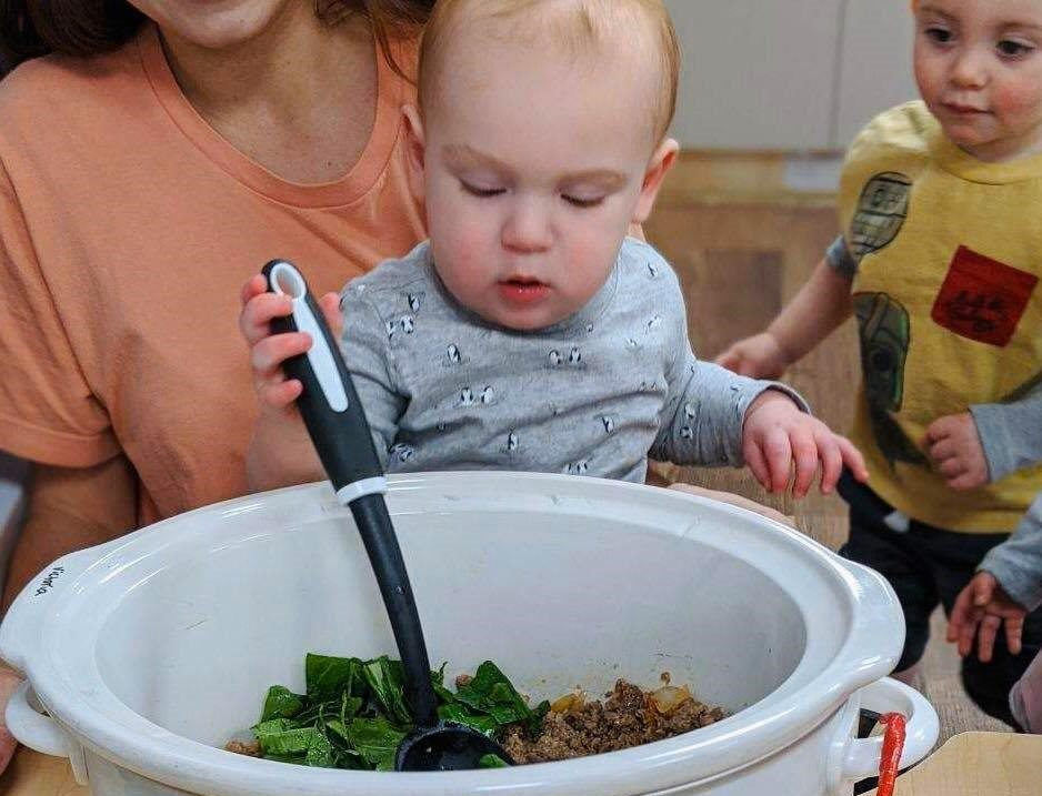 A toddler being watched by another one and a teacher mixing some leafy vegetables and cooked ground pork in a bowl using a spatula at a Preschool & Daycare Serving Hampton Roads, VA