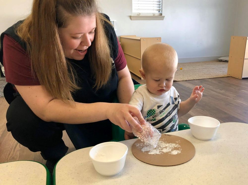 Teacher guiding a toddler putting some white powder on a brown plate at a Preschool & Daycare Serving Hampton Roads, VA