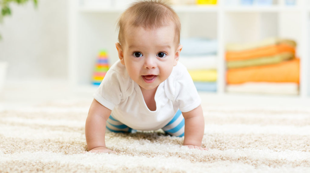 Nursery baby boy crawling on floor indoors at home at a Preschool & Daycare Serving Hampton Roads, VA