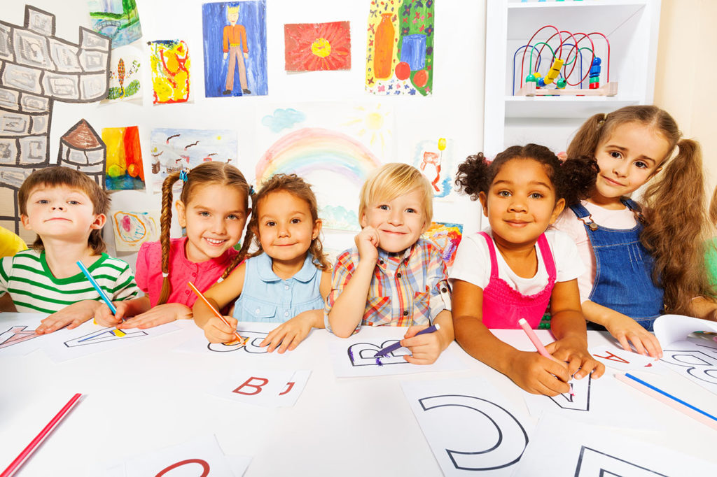 Group of diverse looking boys and girls in kindergarten class drawing letters in early reading class at a Preschool & Daycare Serving Hampton Roads, VA