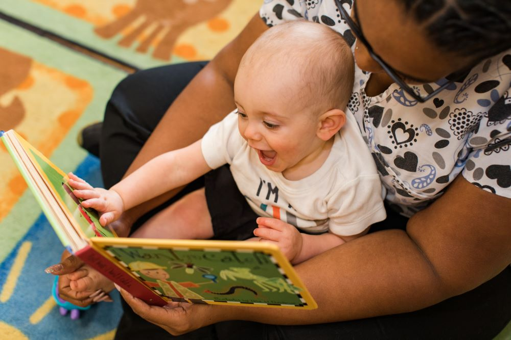 Happy cute little baby boy enjoying the storytelling of the teacher at a Preschool & Daycare Serving Hampton Roads, VA