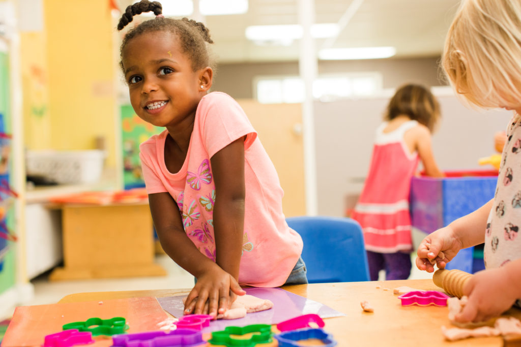 Smiling african american nursery girl pushing a clay on the table while on their clay art activity at a Preschool & Daycare Serving Hampton Roads, VA