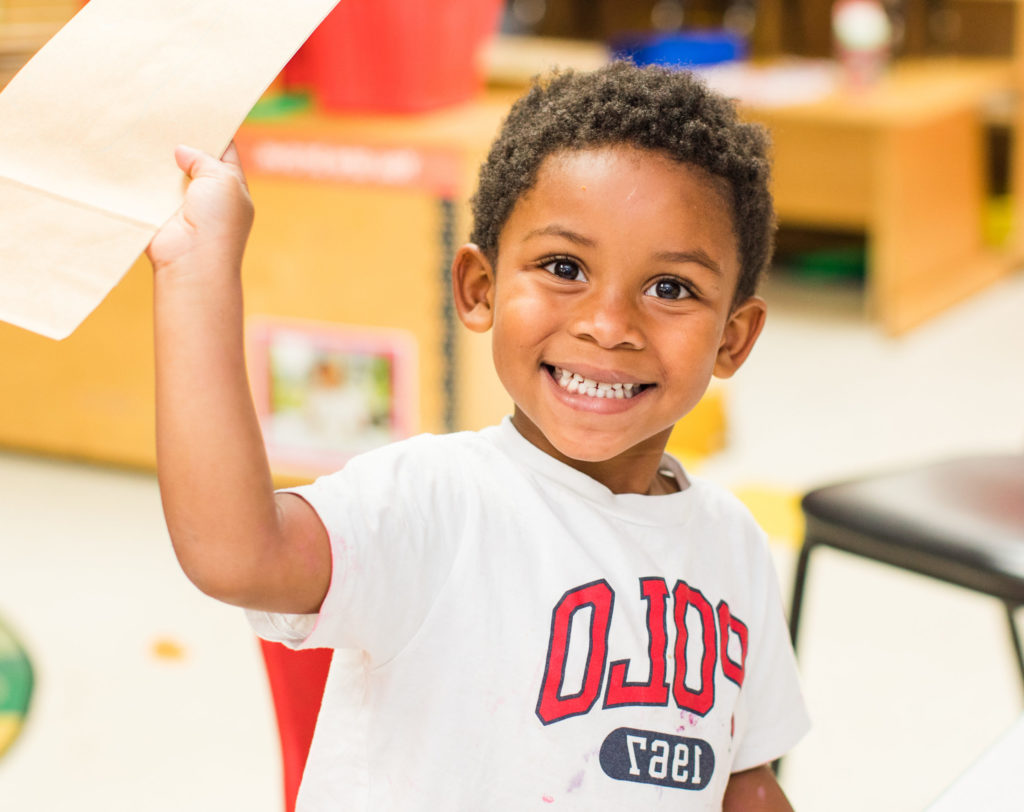 Happy african american nursery boy raising his hands while holding a paper at a Preschool & Daycare Serving Hampton Roads, VA