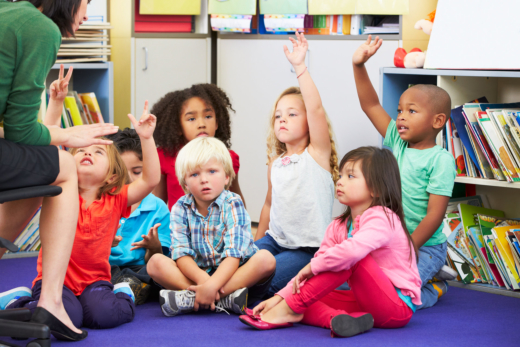 Group of preschoolers paying attention and trying to answer the teachers question at a Preschool & Daycare Serving Hampton Roads, VA