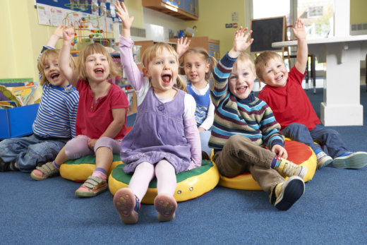 Group of preschool kids happily raising their hands for a school activity while sitting on air pillows at a Preschool & Daycare Serving Hampton Roads, VA