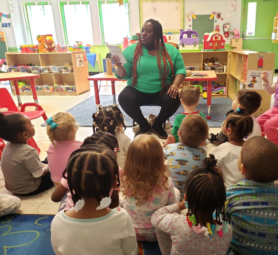 Preschooler listening attentively to their teacher while reading them a story at a Preschool & Daycare Serving Hampton Roads, VA