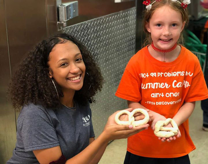Teacher and a young girl holding a Pretzel for a school project at a Preschool & Daycare Serving Hampton Roads, VA