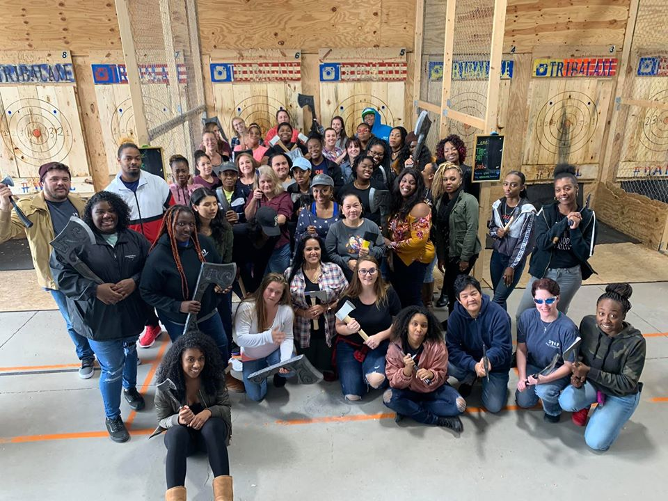 Teachers and parents gather around to do a group selfie while holding their Axe props at a Preschool & Daycare Serving Hampton Roads, VA
