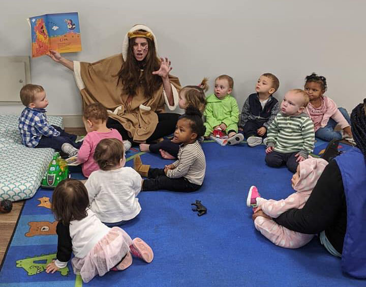 Teacher wearing an animal props doing a story telling to a group of toddlers at a Preschool & Daycare Serving Hampton Roads, VA