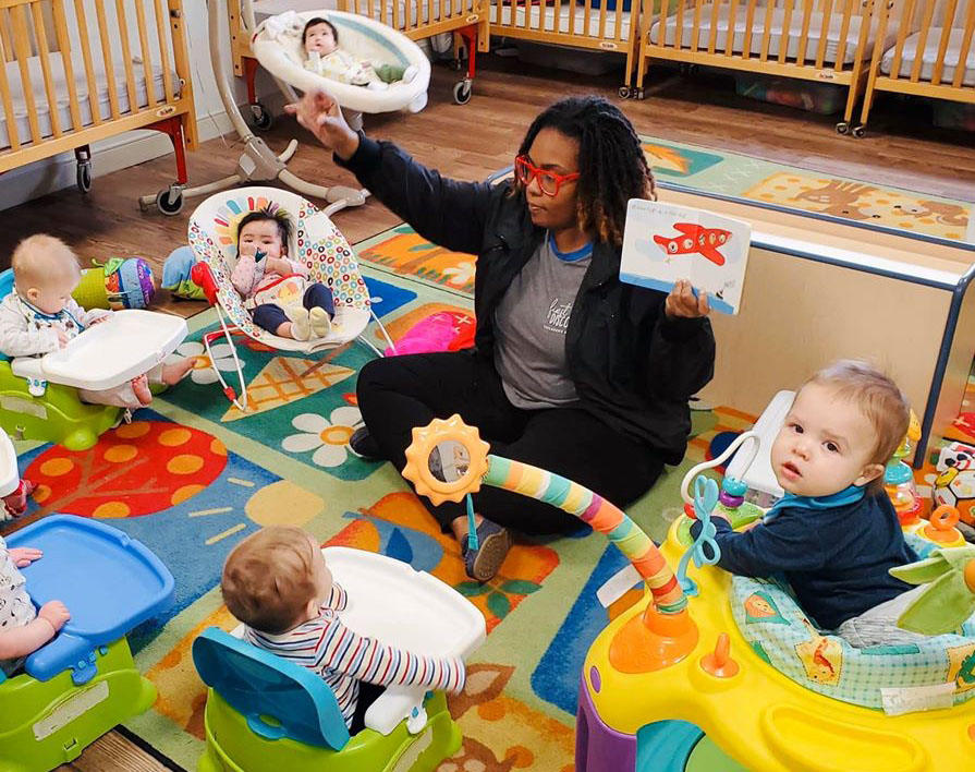 Teacher showing the babies around her some colorful pictures at a Preschool & Daycare Serving Hampton Roads, VA